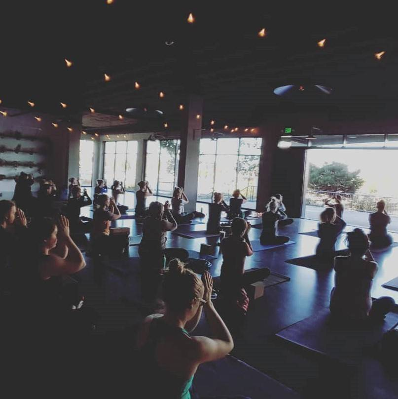 Full yoga class under white string lights facing a wall of windows