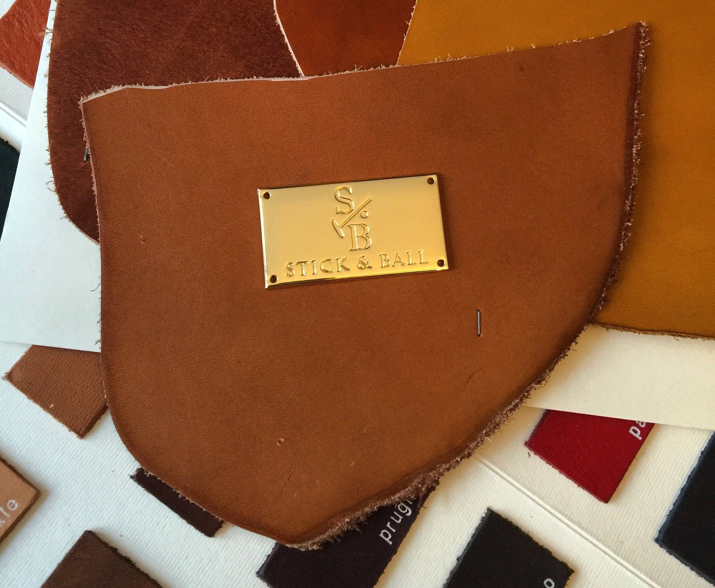 Design sample of the Stick & Ball logo gold plate on vegetable-tanned leather