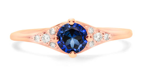 Engagement ring in pink gold with sapphire as the main stone surrounded by 8 small diamonds of different sizes.