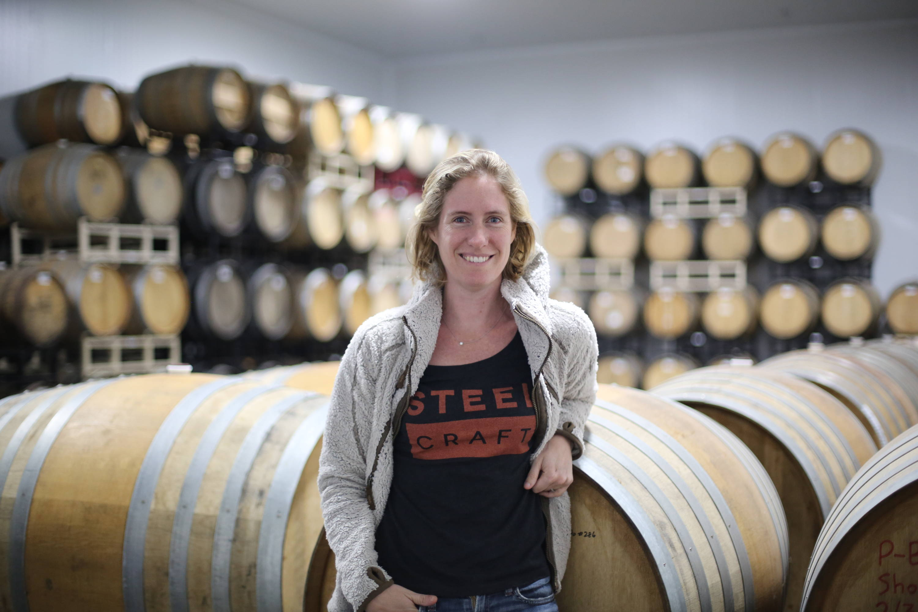 Owner, Laurie Porter, leaning on a wine barrel in a room full of barrels.