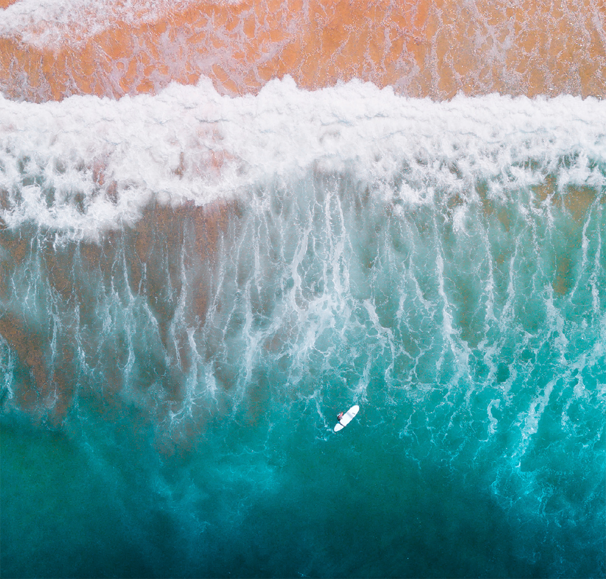 Arial shot of beach shore, a person is surfing. Evgeniya Savina/Stocksy