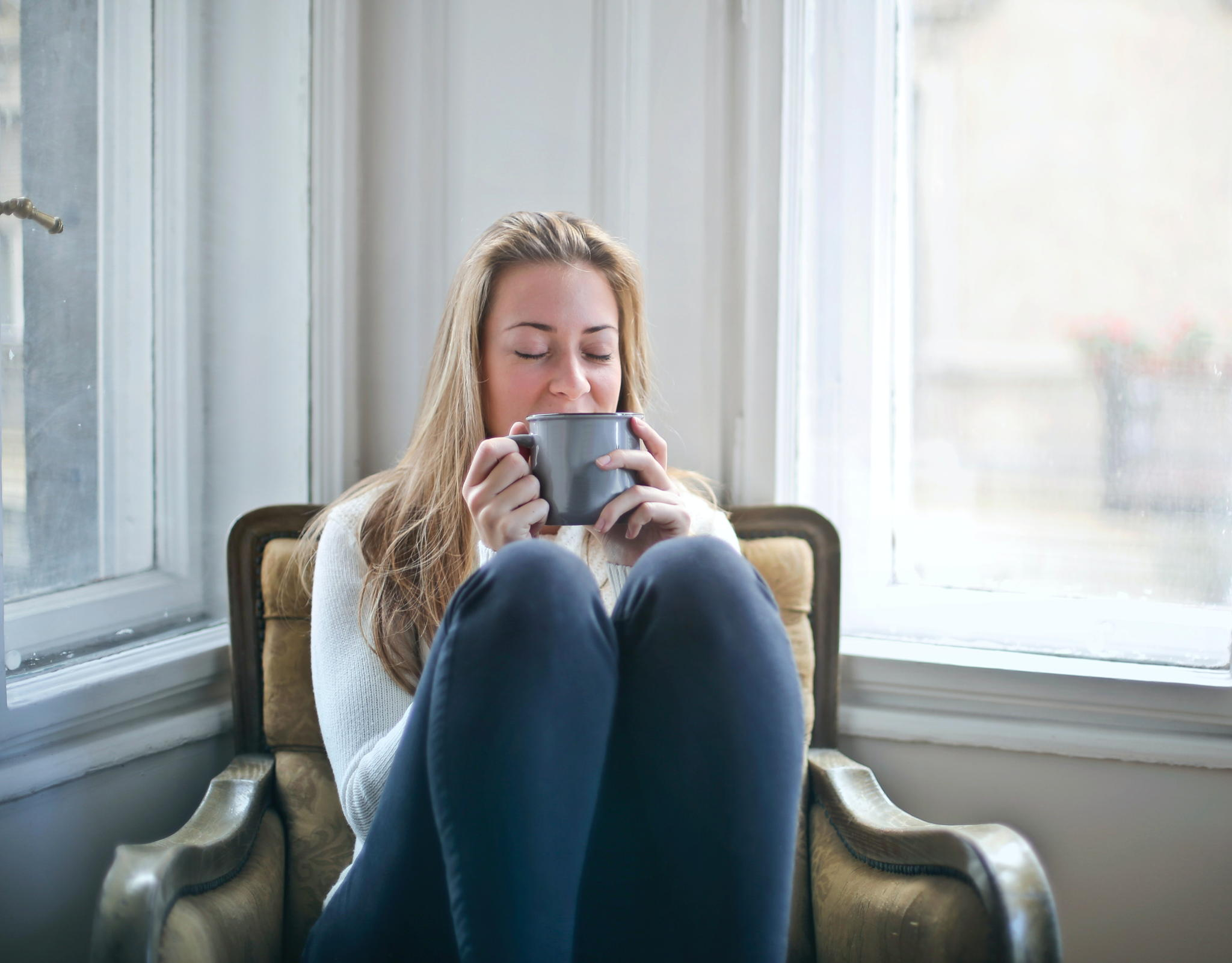 A blond haired woman is sitting with her knees up on a chair with a coffee mug close to her nose.