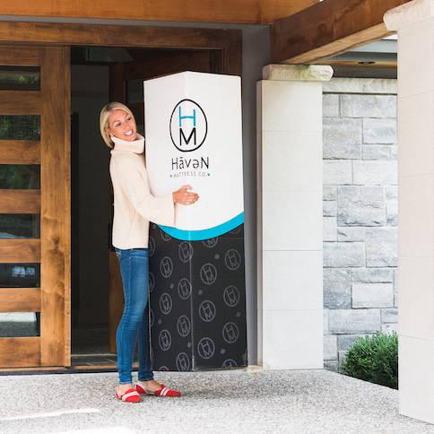 Sarah Baeumler holding a Haven Sleep Co mattress box on her doorstep.