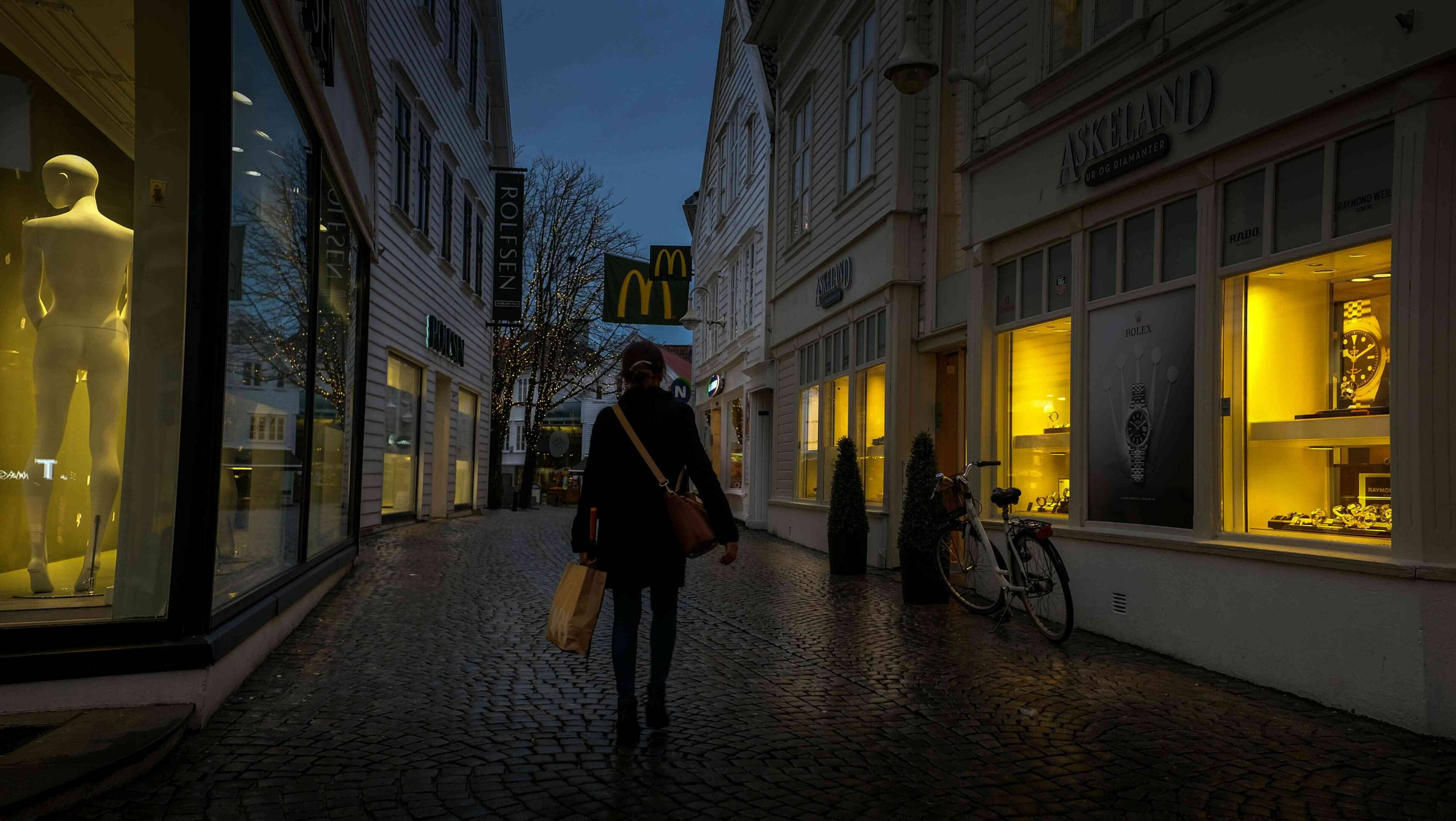 Lady walking through the high street at night past shops to stay safe alone