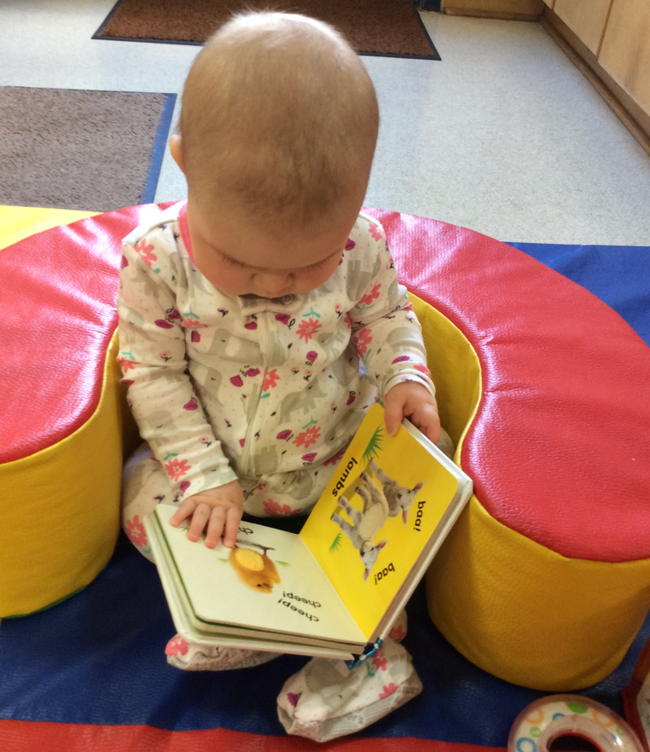 infant reads book