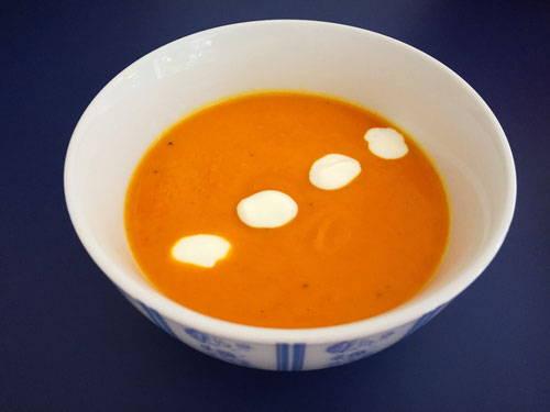 Porzellanschüssel mit Kürbissuppe und drei kleinen weißen Klecksen Naturjoghurt