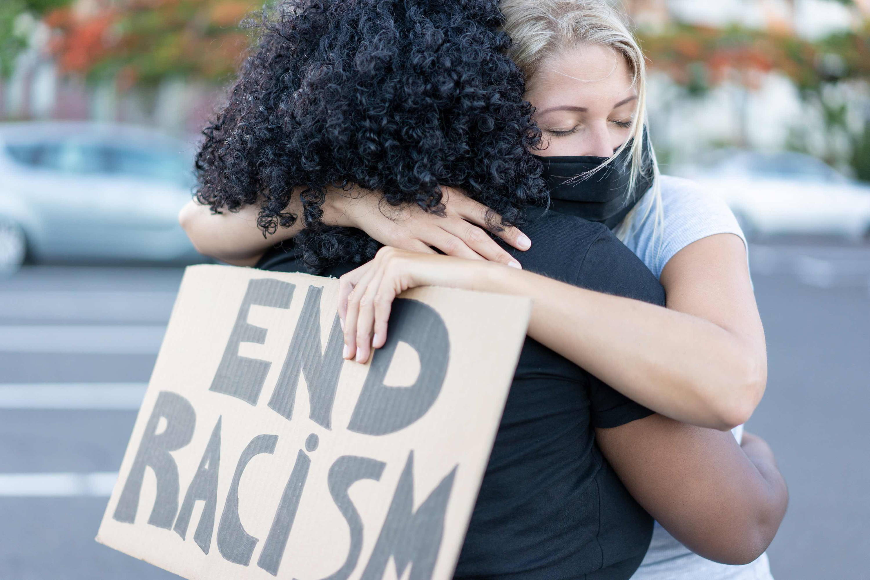 Black and white woman embrace holding End Racism placard