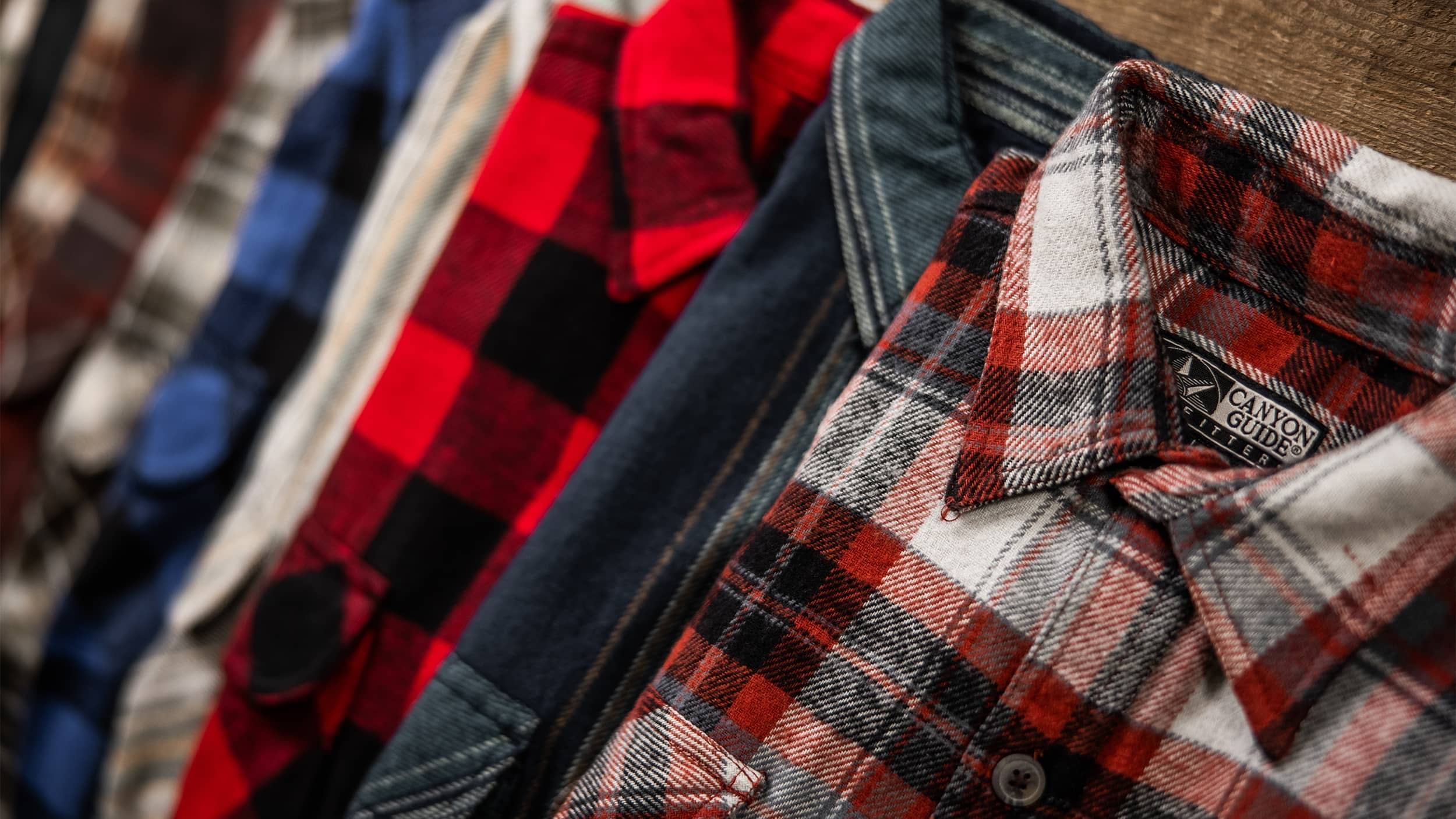 7 flannel lined up in a row