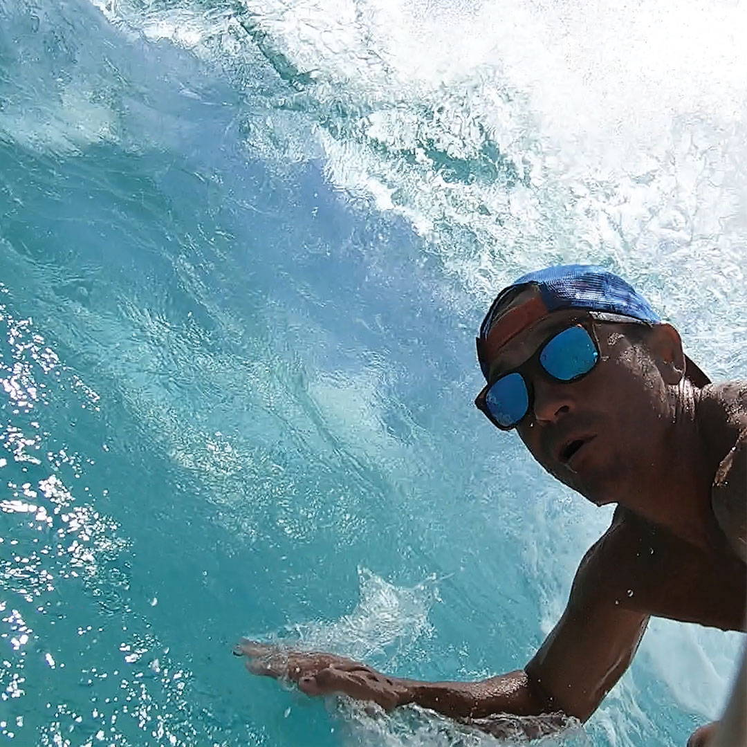 A surfer wears Rheos floating sunglasses inside a barrel.