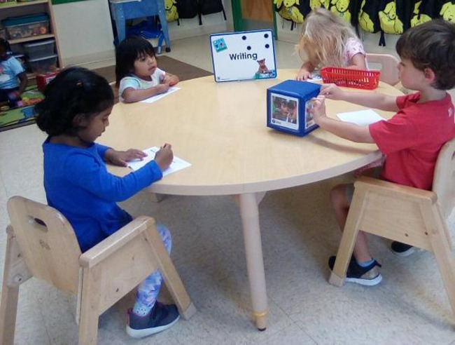 Children sitting at a table using crayons on paper