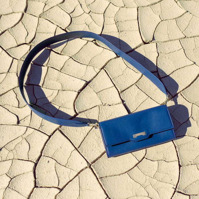 Dark blue vegan leather crossbody mini handbag wallet on the sand in the desert of California