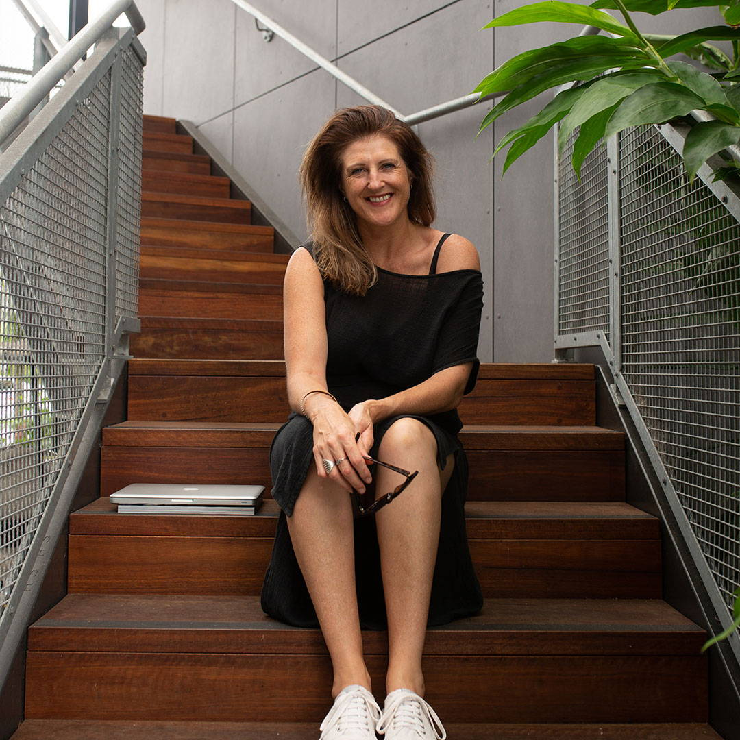 smiling brunette woman wearing a black dress and white sneakers sitting on wooden stairs