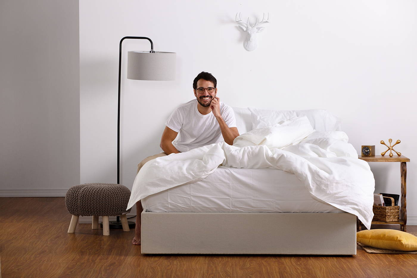 Man in bed with stylishly decorated room. Image