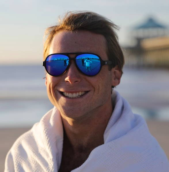 Lejend stays warm after a swim in the ocean, and wraps himself in a blanket and his Rheos Palmettos sunglasses.