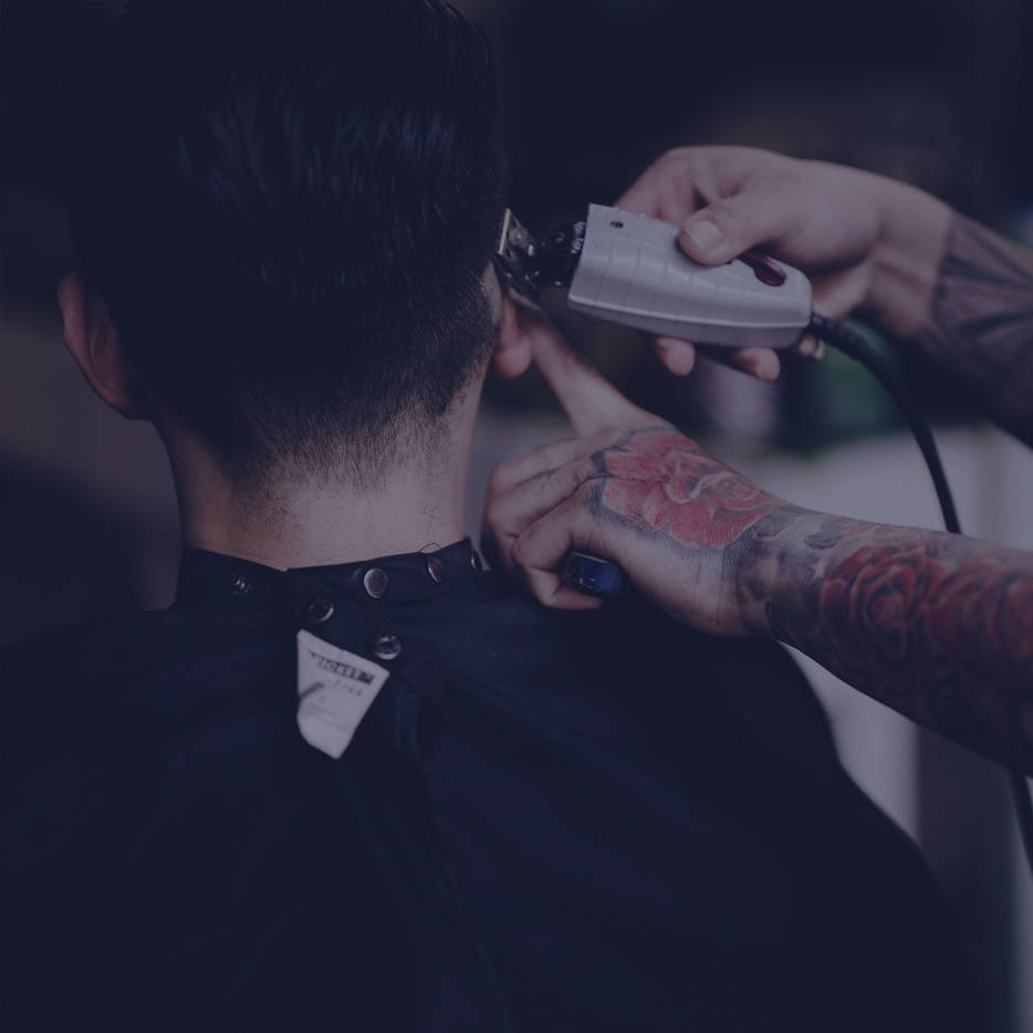 Barber using clippers on a customer