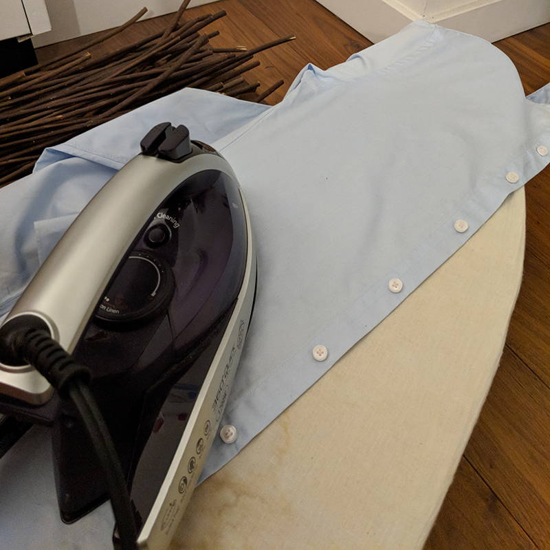 front flap slim dress shirt on ironing board with iron over