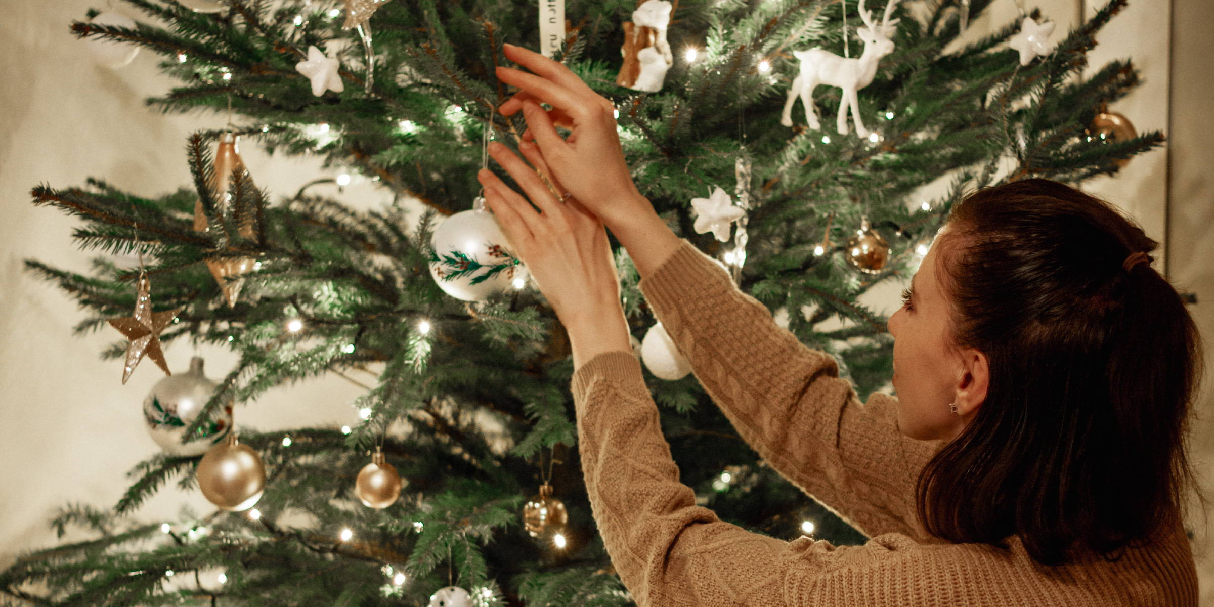 Woman decorating a Christmas tree surrounded by her friends and family paired perfectly with Kiss of Wine canned wine.