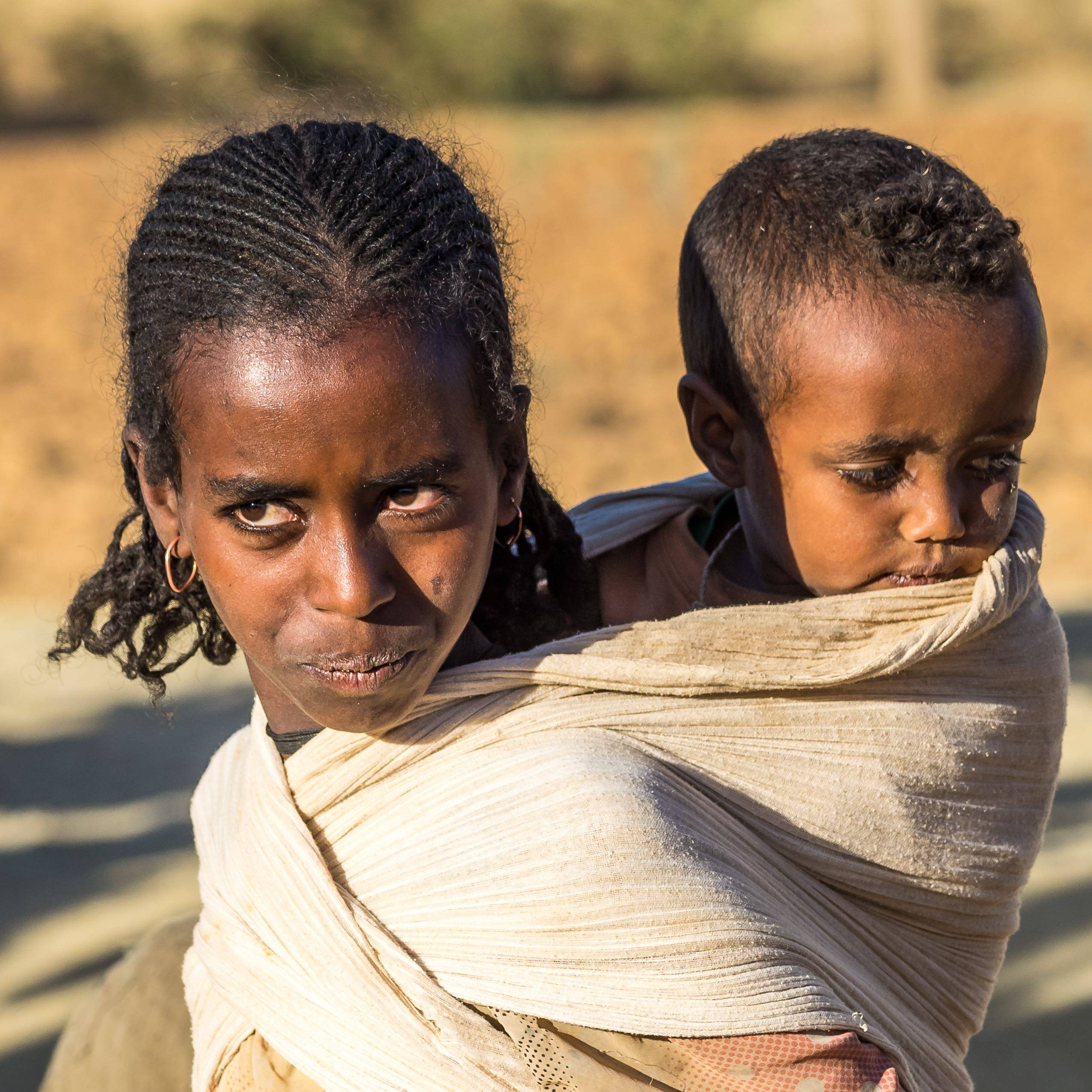 Ethiopian girl with child on her back on roadside in Tigray