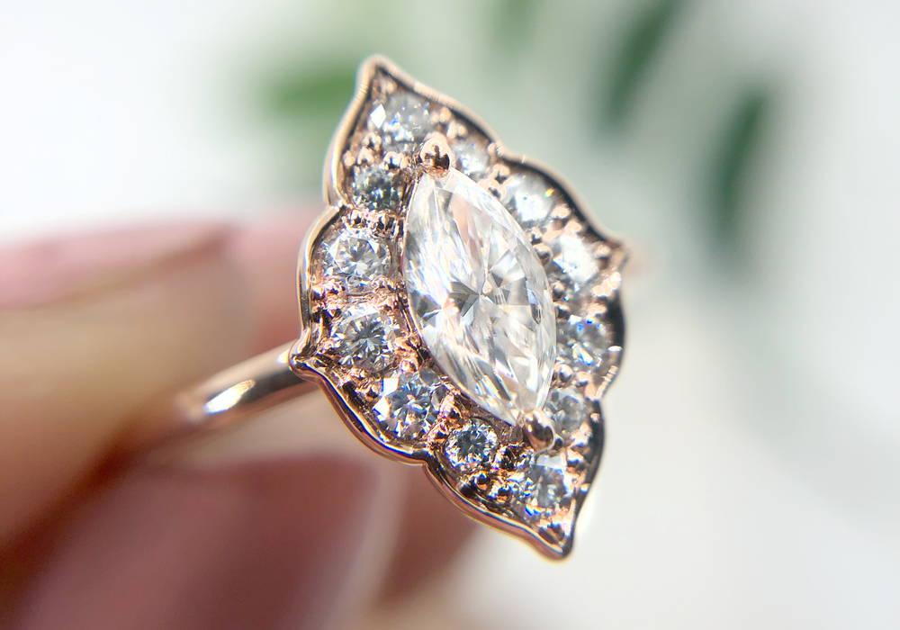 Bague de fiançailles au design unique avec un diamant marquise de 0.37 ct. Le centre est entouré d'un pavé de 12 diamants qui accentue sa brillance.