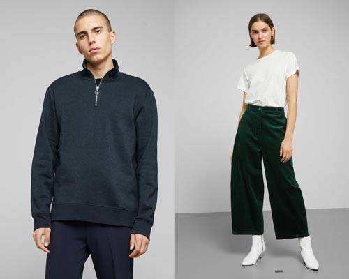 Man wearing dark navy blue quarter zip organic cotton jumper with navy trousers and woman wearing white organic cotton t-shirt tucked into organic cotton green wide leg cords with white heeled ankle boots from sustainable fashion brand Weekday