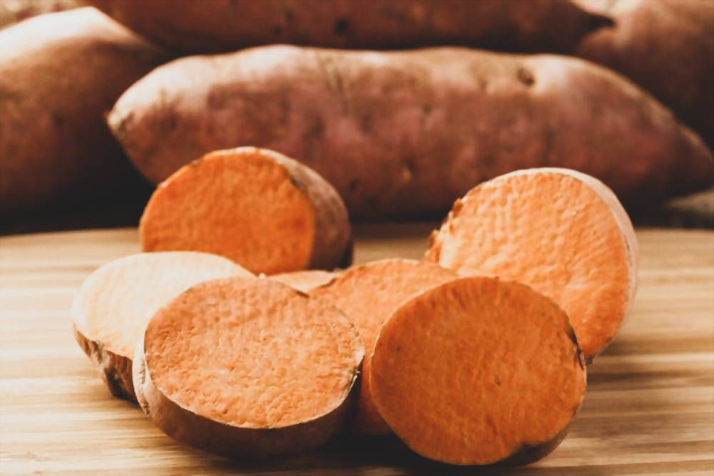 Slice sweet potatoes on wooden cutting board