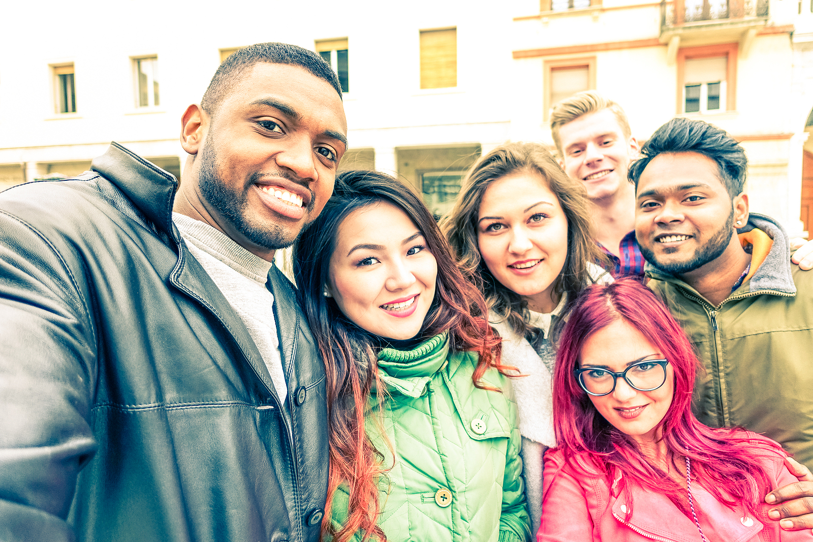 Image of a multiracial group of 6 friends dressed for the winter, all taking a selfie in the street smiling.