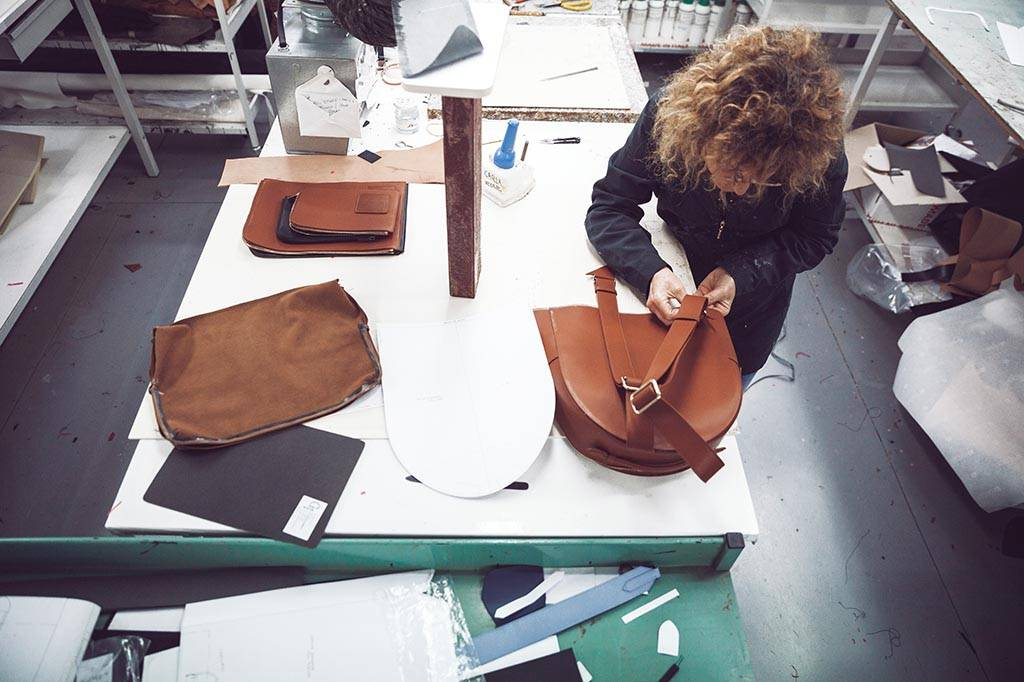 Woman in a factory in Florence assembling an Opus Mind bag using upcycled leather