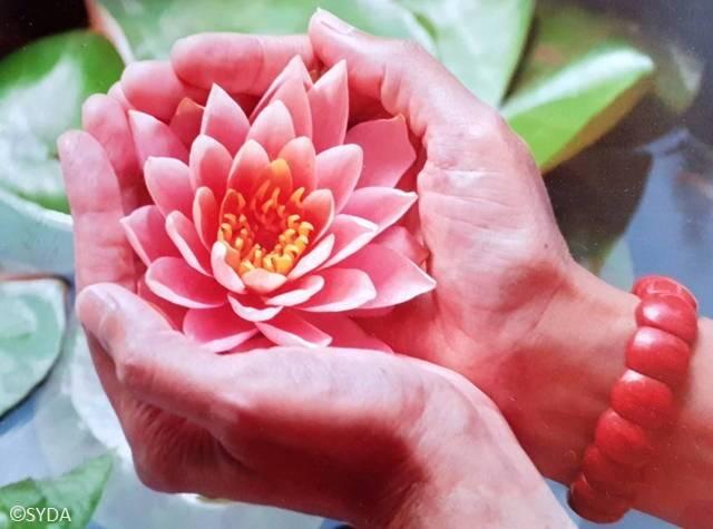 Gurumayi holding a lotus flower