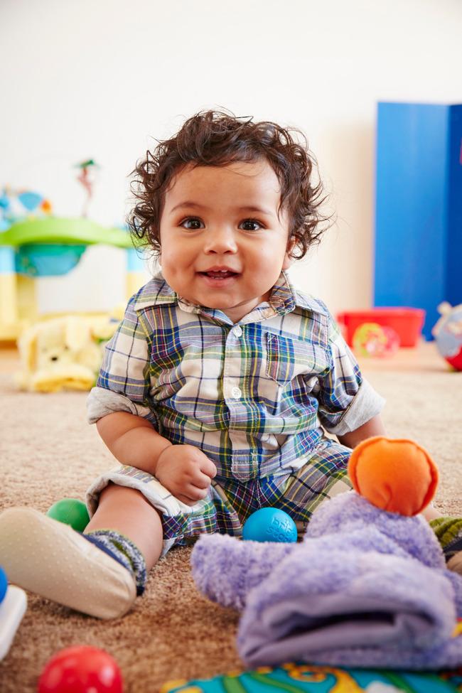 child smiling and sitting on gfloor