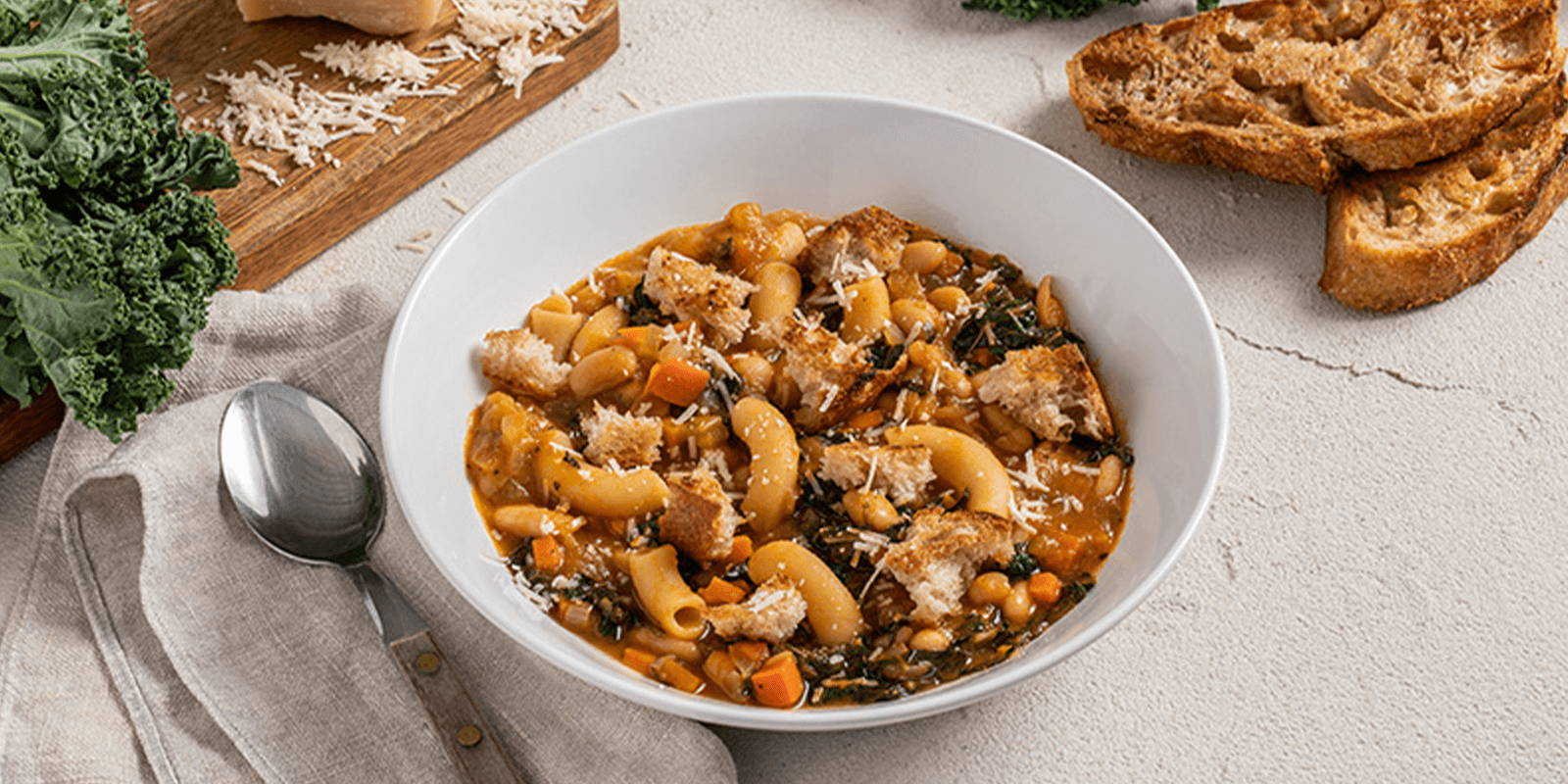 Added alt tag: A bowl of ribollita soup filled with ZENB Elbows Pasta garnished with cheese.