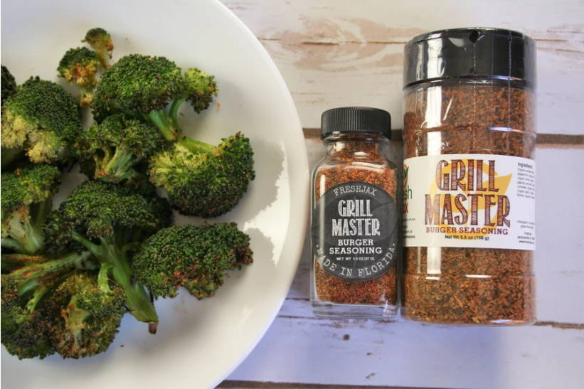 A plate of Grill Master Roasted Broccoli next to a sample and large bottle of Freshjax Grill Master Burger Blend.