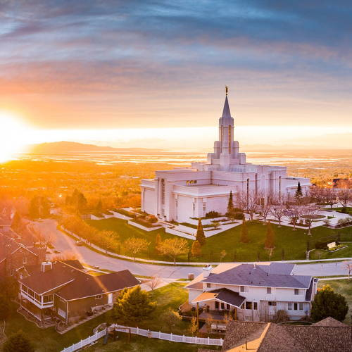 Photo of the Bountiful Temple next to a sunburst just above the mountains.