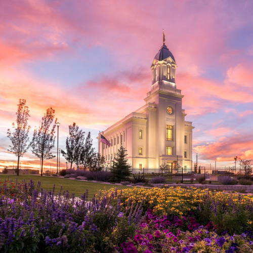 Cedar City glowing against a sunset sky. Flower bed in forefront.