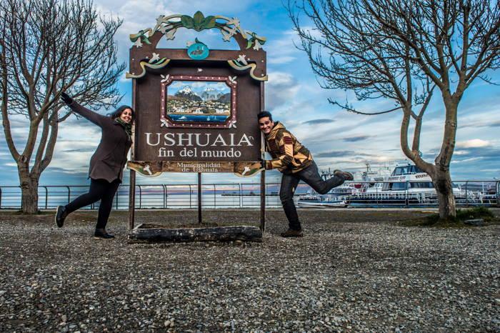 casal na placa da cidade Ushuaia fin del mundo