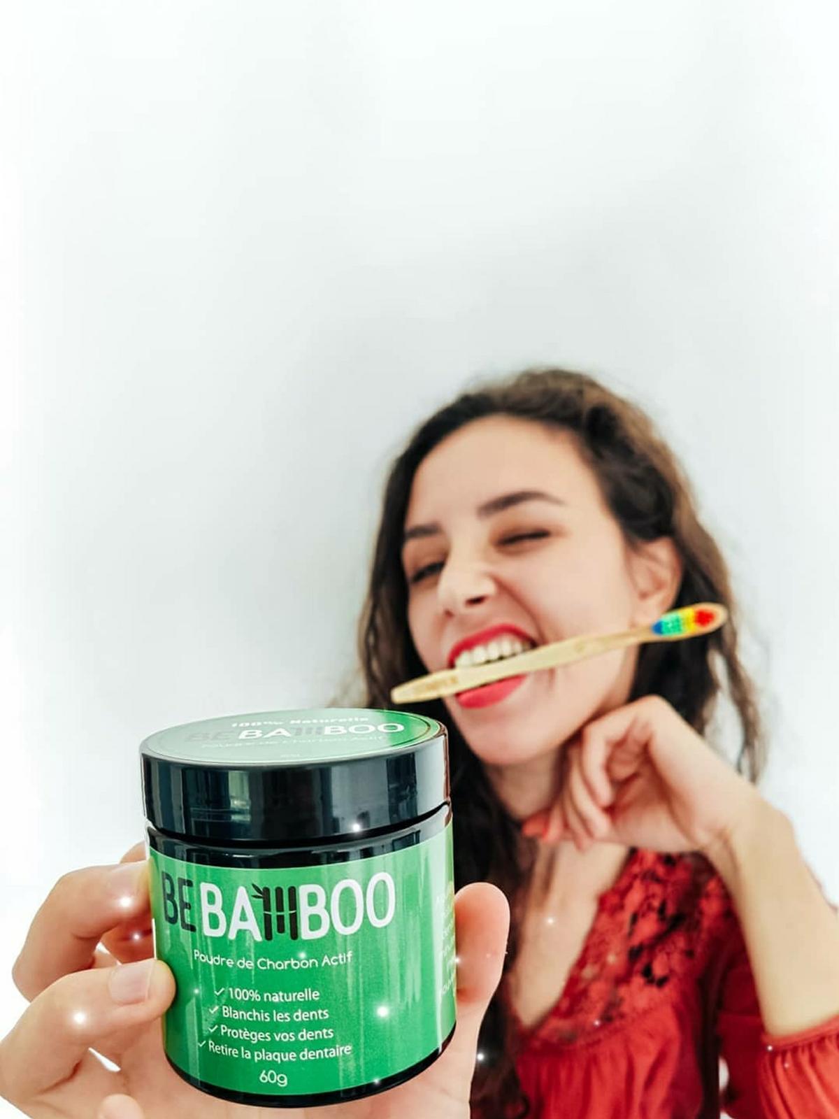 Jeune femme tenant un pot de poudre de charbon dans la main et une brosse à dents en bambou dans la bouche