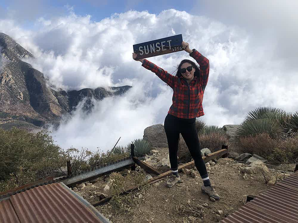 Woman holding a wood sign saying Sunset at Sunset Peak in the San Gabriel Mountains