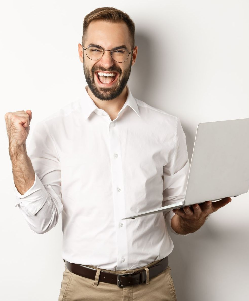 Business happy manager winning online rejoicing with fist pump holding laptop triumphing standing