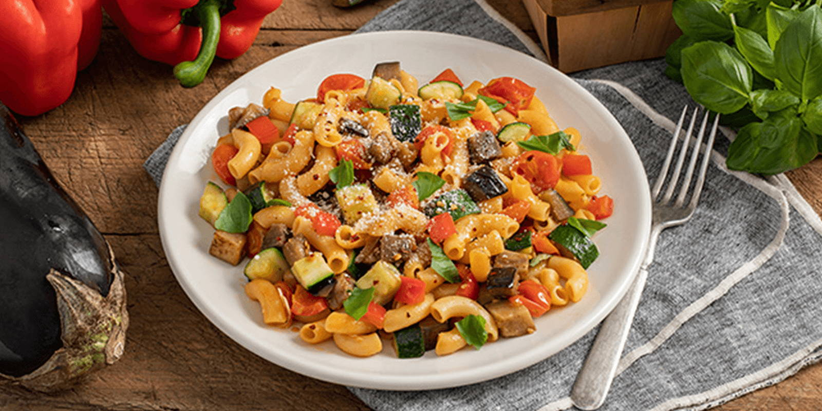 Bowl of pasta with chopped vegetables on a counter with whole vegetables.