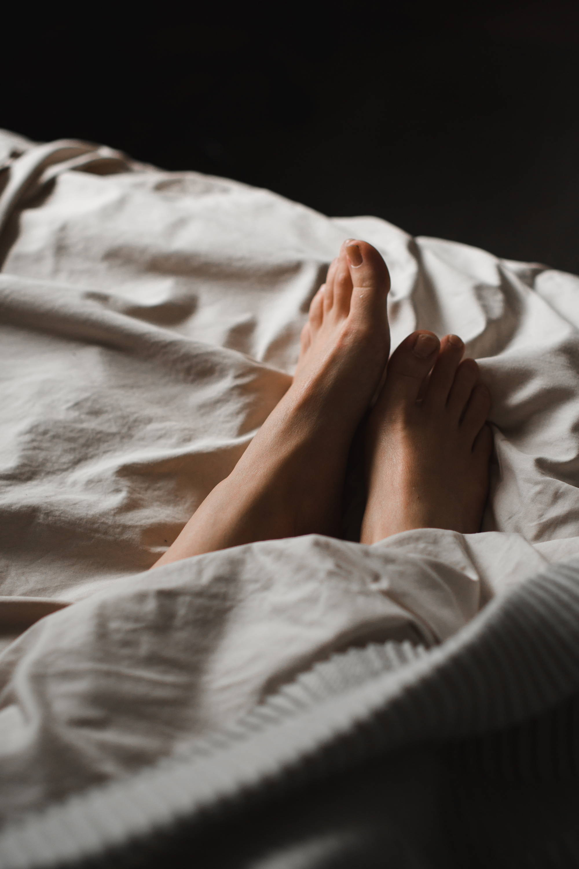 Crop unrecognisable female feet lying in cozy bed - Photo by Владимир Гладков from Pexels