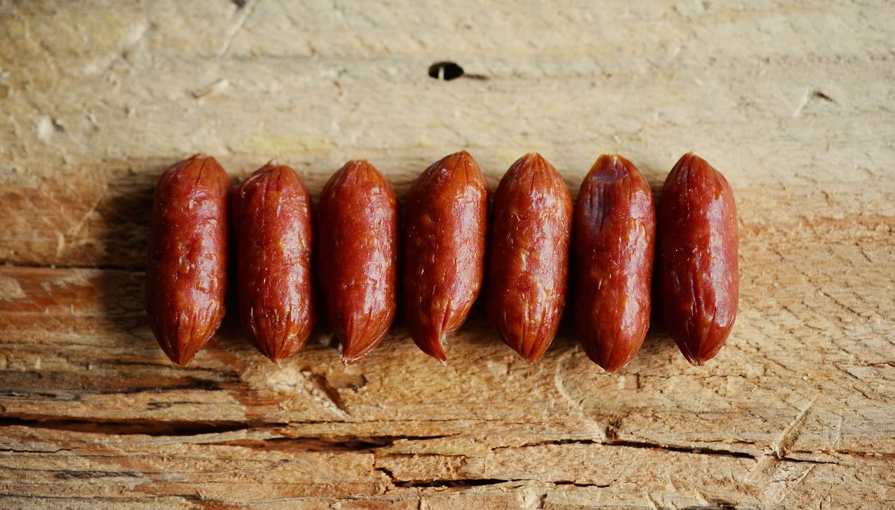 a row of little sausages on a serving board