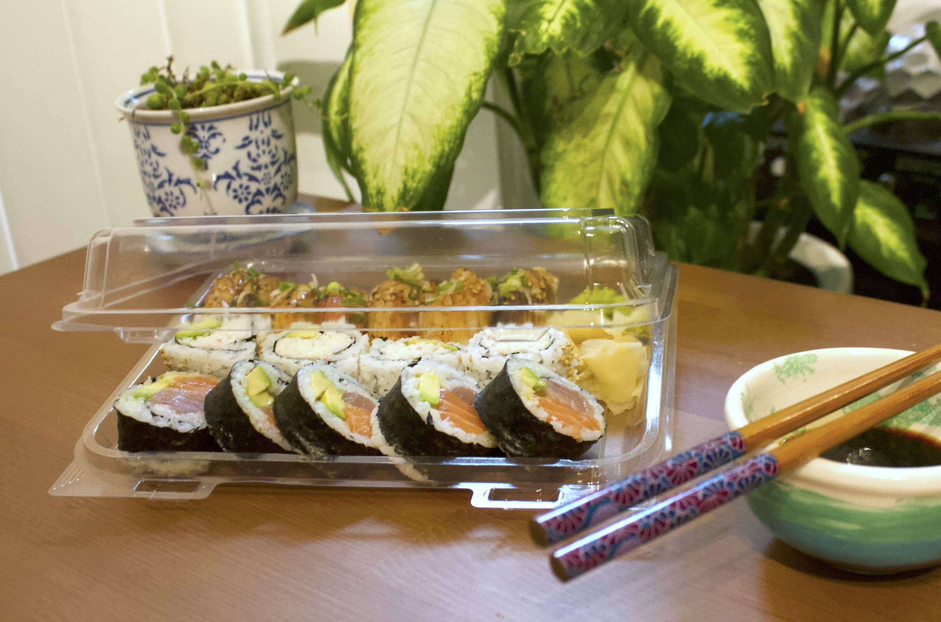 compostable carry-out container of sushi at table