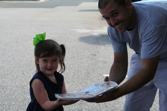 Father and daughter holding pizza