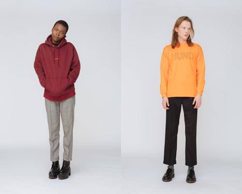 Woman wearing burgundy organic cotton hooded sweatshirt with grey cropped trousers and man wearing bright orange long sleeve tee with black cropped trousers from sustainable fashion brand Hund Hund