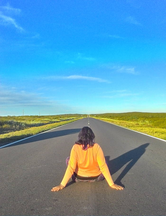 garota sentada no chão no meia da estrada