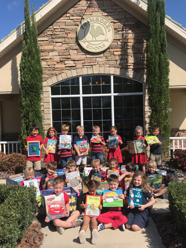 photo of the Kindergarten class surrounded by all of the books donated to Mothers Helping Mothers