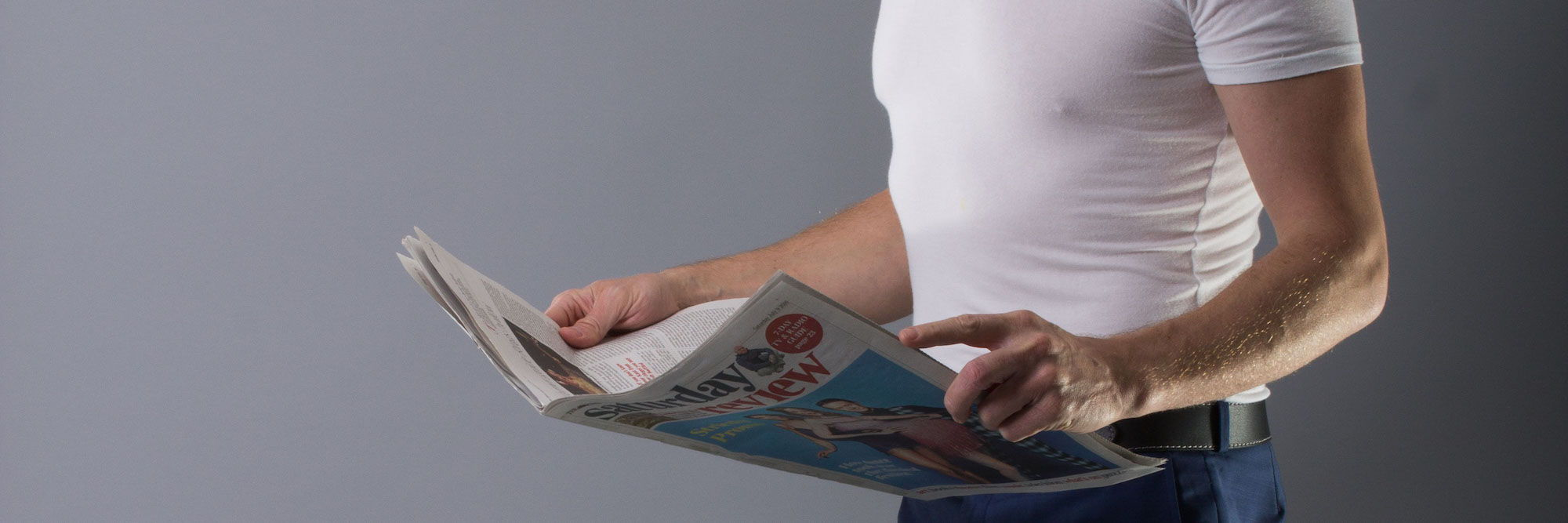Image of a man wearing an undershirt whilst reading a newspaper