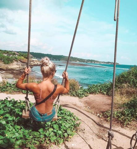 backview of a blonde woman on a swing on a tropical beach