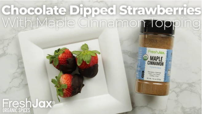 A plate of chocolate cover strawberries next to a large bottle of FreshJax Organic Maple Cinnamon Topping.
