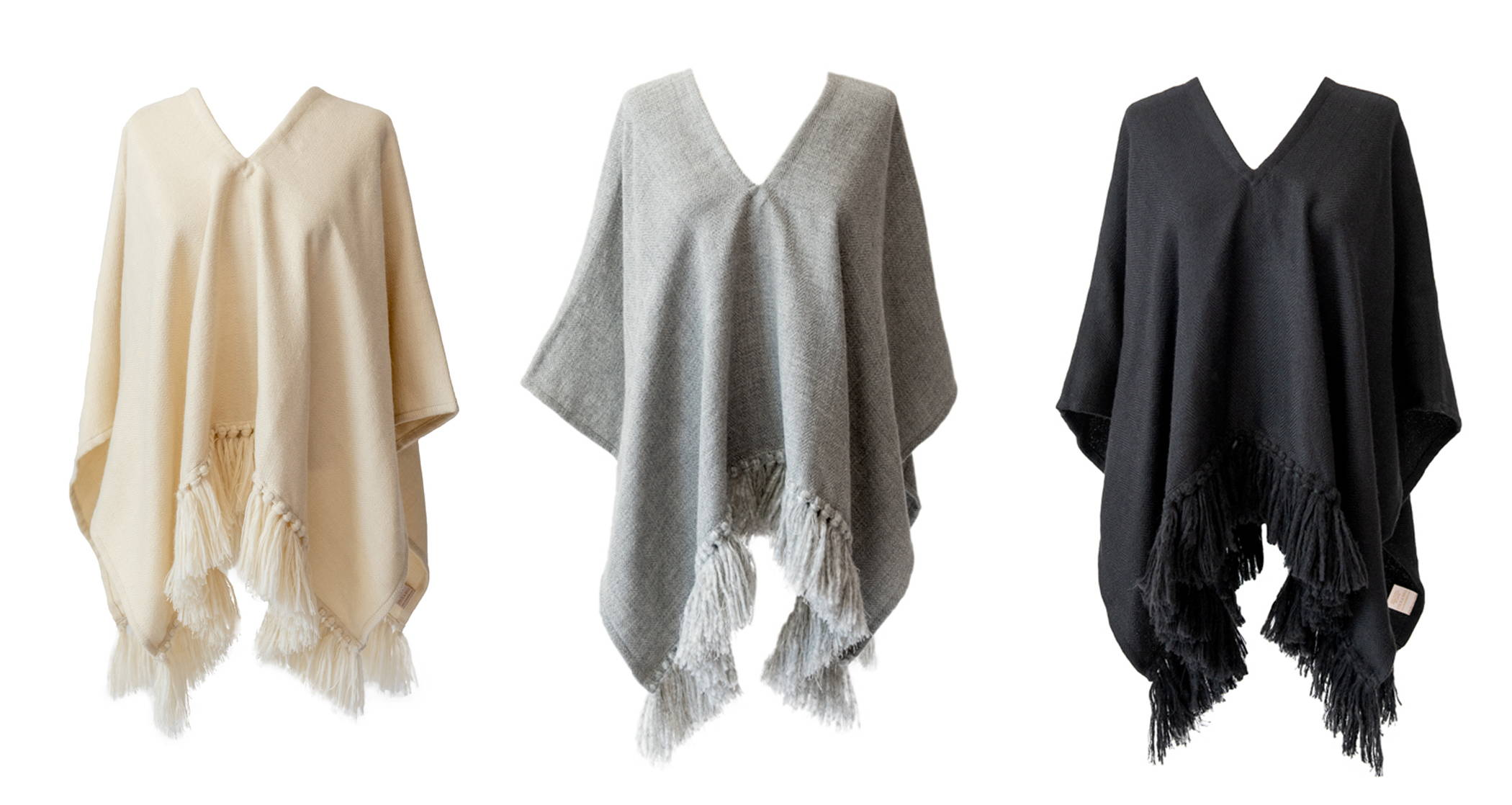 Display of herringbone handwoven Cropped Fringe Alpaca ponchos in cream, light grey & black