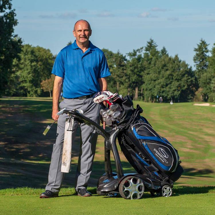 Golfer with Stewart Golf trolley.